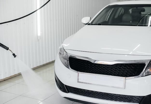 Lavagem moderna com espuma e água de alta pressão de um carro branco