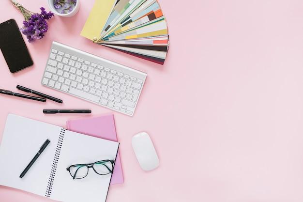 Lavanda; celular; teclado e mouse com artigos de papelaria do escritório no fundo rosa colorido