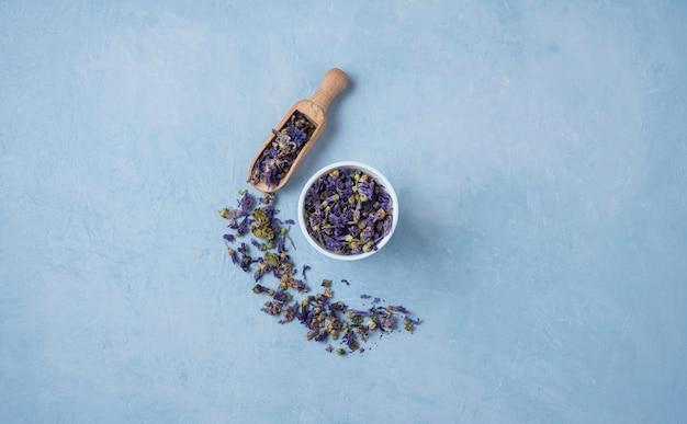Lavanda e camomila aromática chá seco de ervas soltas perto de copo branco na mesa de madeira azul