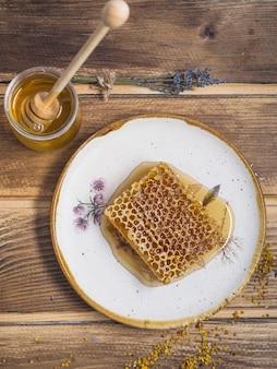 Lavanda; pote de mel com mel de madeira e pólen de abelha na mesa de madeira