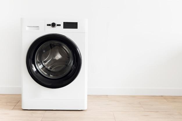 Lavanderia branca com uma máquina de lavar roupa copie o espaço