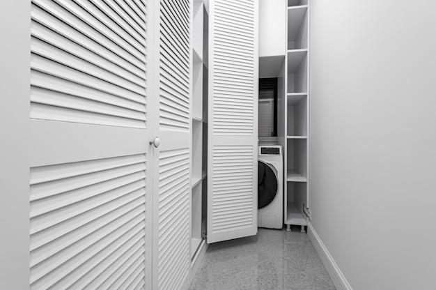 Lavanderia branca dentro da sala do guarda-roupa no apartamento novo