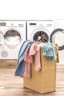 Lavanderia com cesta e lavar e secar máquinas no fundo