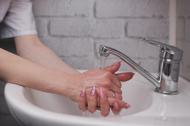 Lavando as mãos na pia do banheiro, higienização das mãos do homem para precaução de pandemia do vírus corona, lavando as mãos com frequência