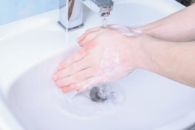Lavando as mãos na pia esfregando com sabonete para vírus corona