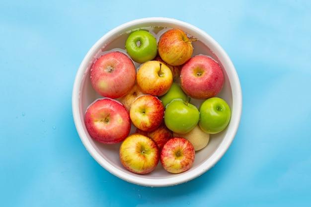 Lavando maçãs frescas na água em uma tigela
