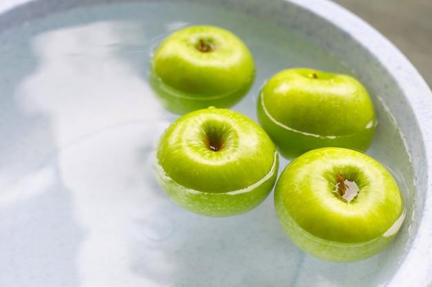 Lavando maçãs verdes frescas na água