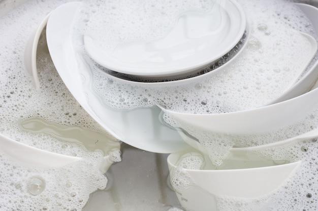 Lavando pratos, close-up de utensílios de imersão na pia da cozinha.