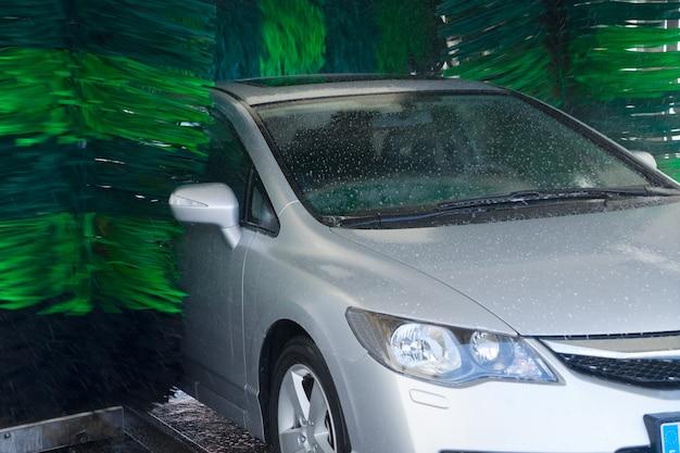 Lavando um carro cinza com água de perto