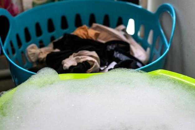 Lavar a roupa à mão com espuma detergente.