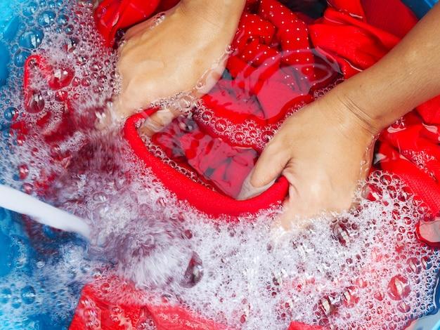 Lavar a roupa com as mãos usando detergentes, molhe o tecido vermelho em detergente para a roupa e água da água da torneira no lavatório azul.