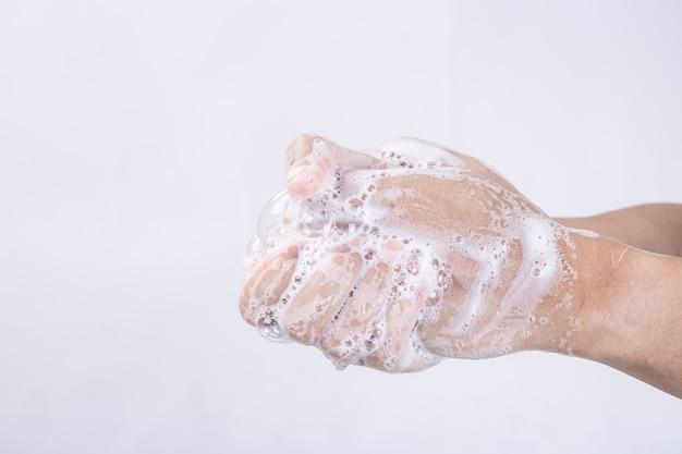 Lavar as mãos com água quente e sabão em casa pia banheiro homem limpar a higiene das mãos para prevenção de surtos de coronavírus.