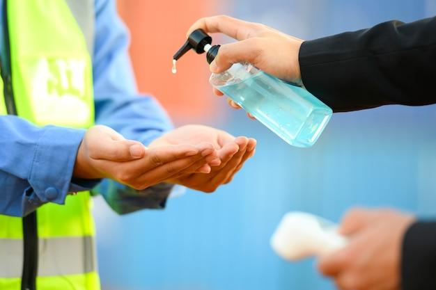 Lavar as mãos com álcool desinfetante e medir a temperatura com um termômetro de funcionário antes de entrar no trabalho. previna a infecção por coronavírus (covid-19)