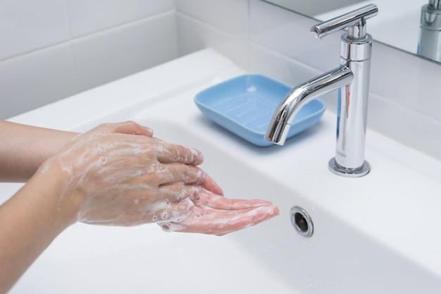 Lavar as mãos com sabão sob água corrente