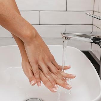 Lavar as mãos esfregando com sabão e água da torneira