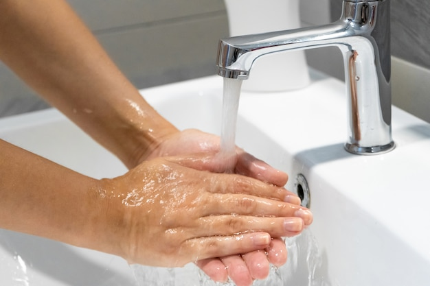 Lavar as mãos esfregando com sabão mulher para prevenção do vírus da coroa, higiene para parar de espalhar o coronavírus