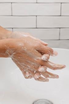 Lavar as mãos esfregando com sabonete lateralmente