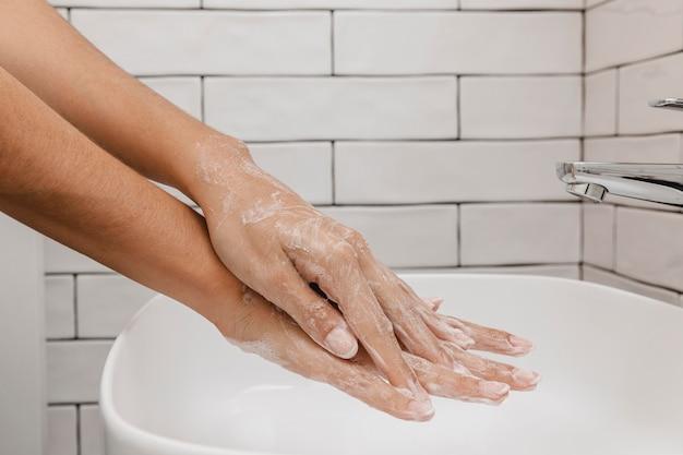 Lavar as mãos esfregando com sabonete vista lateral