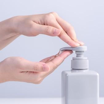 Lavar as mãos. mulher jovem asiática usando sabonete líquido para lavar as mãos, conceito de higiene para parar de espalhar o coronavírus isolado no fundo branco cinza, close-up.