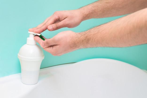 Lavar e desinfetar as mãos de germes e vírus usando espuma de sabão e jato de água sobre um fundo azul. pandemia de coronavírus, proteção à saúde pessoal.