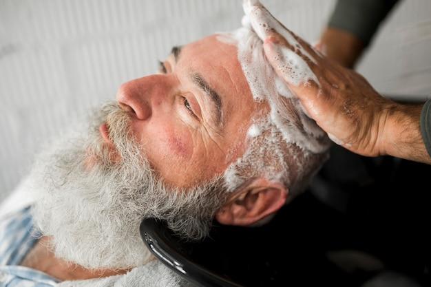 Lavar o cabelo do homem idoso na barbearia