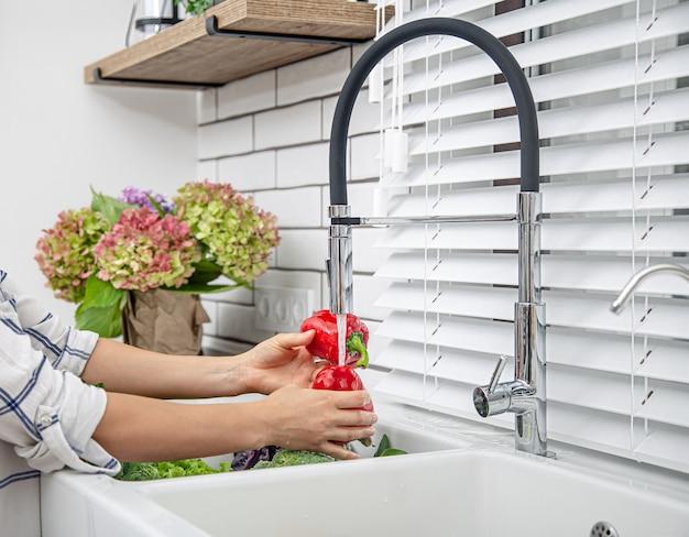 Lavar o pimentão com água da torneira. o conceito de produtos naturais limpos, lavados à mão.