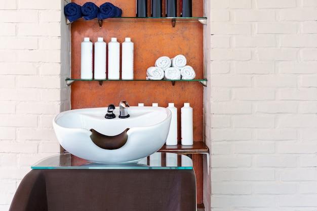 Lavar pia para lavar o cabelo em salão de beleza ou barbearia, shampoos, toalhas. espaço de trabalho do estilista de cabeleireiro.