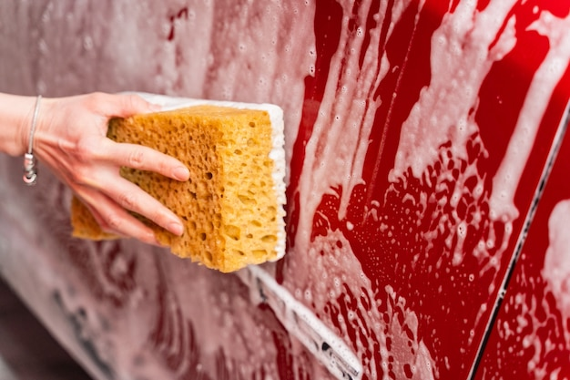 Lavar um carro vermelho com uma esponja amarela espumosa. mão de uma mulher lavando um carro na lavagem de carros.