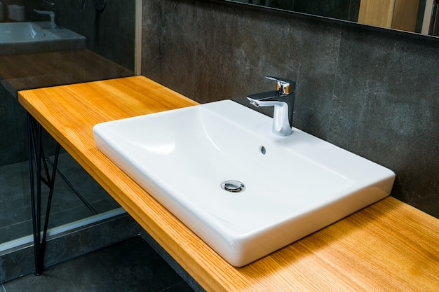 Lavatório com detalhes modernos e contemporâneos do banheiro em uma casa de luxo, toque no lavatório de torneira cromada