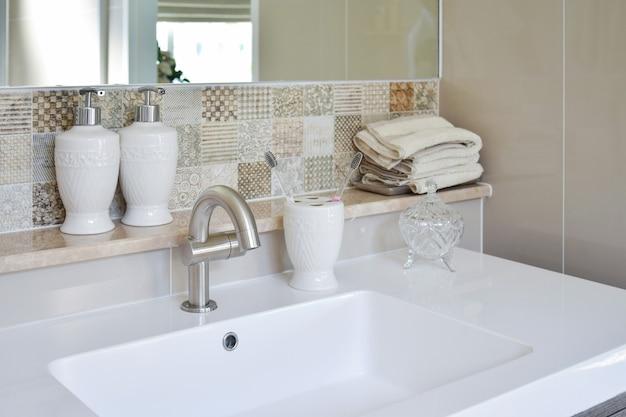 Lavatório com torneira e garrafa de sabonete líquido em casa