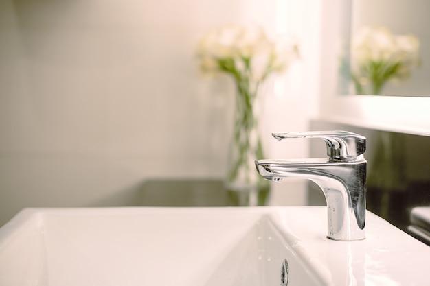 Lavatório de luxo interior de banheiro e torneira em vaso sanitário para lavar as mãos com decoração de flores