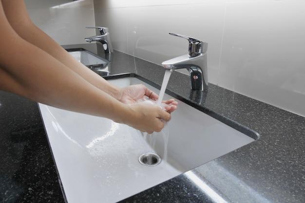 Lavatório e torneira branco no balcão de granito com lavagem das mãos