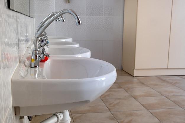 Lavatórios de cerâmica branca com torneira de água de aço inoxidável brilhante.