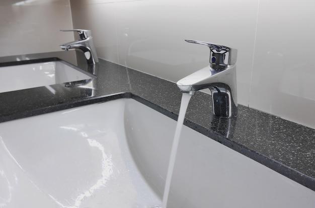 Lavatórios e torneira brancos no balcão de granito com gota de água