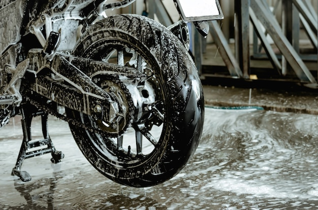 Lave a moto na oficina de lavagem de carros. lavagem de carros em espuma sobre rodas