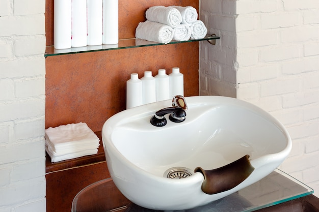 Lave a pia para lavar o cabelo no salão de beleza ou na barbearia. cabeleireiro estilista espaço de trabalho. interior do salão de beleza.