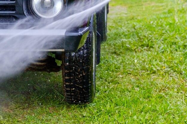 Lave o carro à tarde ao ar livre com um aparelho de alta pressão