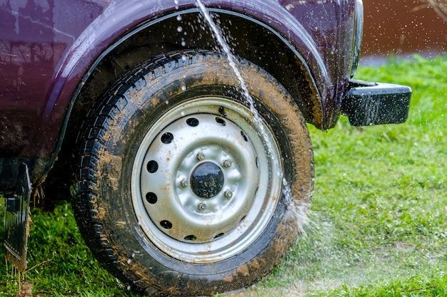 Lave o carro à tarde ao ar livre com um jato de água de uma mangueira de jardim