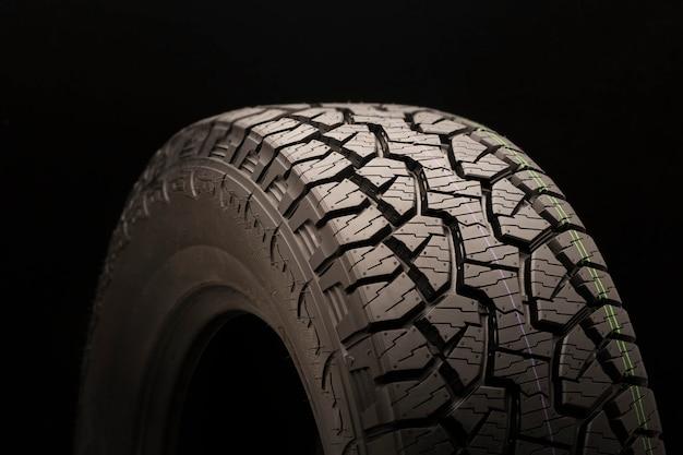 Lave todos os pneus de terreno para suvs em um fundo preto close-up, roda, jogo de luz e sombra