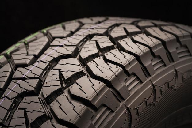 Lave todos os pneus de terreno para suvs em um plano de fundo preto, com ênfase no piso da roda.