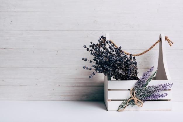 Lavenders na caixa de madeira branca contra o pano de fundo de madeira