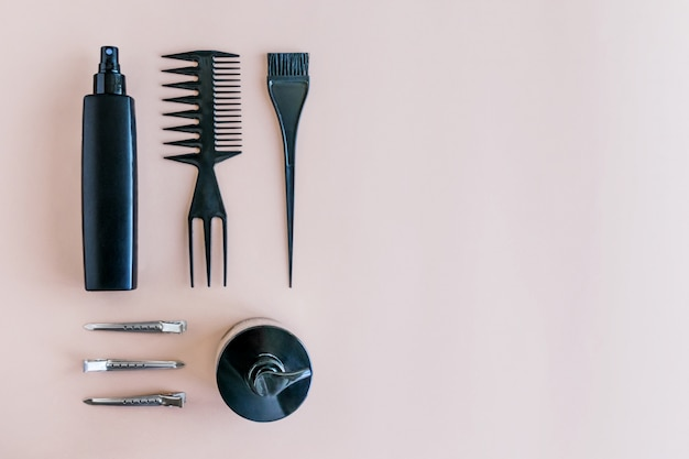 Lay flat composição mínima com ferramentas de cabeleireiro preto no fundo pastel