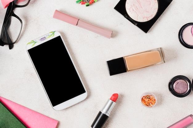 Lay out de produtos de maquiagem e smartphone