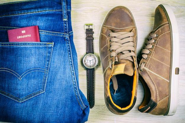 Lay plana. blue jeans, sapatos, passaporte e relógio de pulso