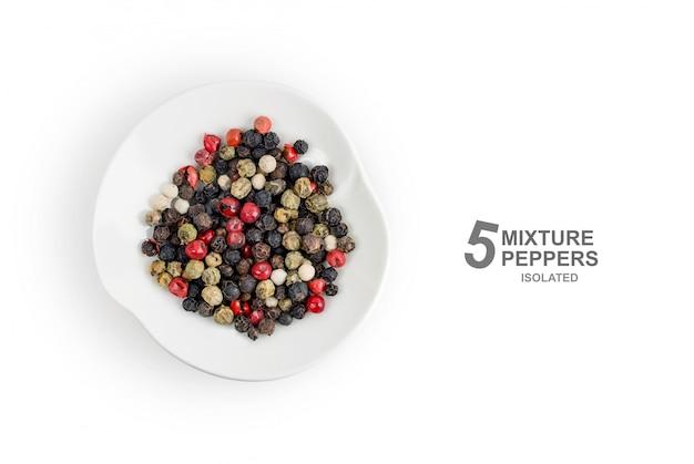 Lay plana. mistura perfumada de cinco tipos de pimentas coloridas aleatórias em uma placa isolada no fundo branco. vista do topo.