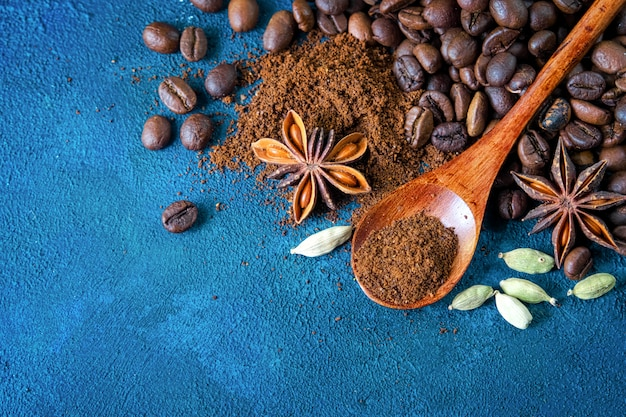 Lay plana. os grãos de café dispersaram em um fundo estrutural azul, estrelas do anis, cardamomo e café à terra em uma colher de madeira.
