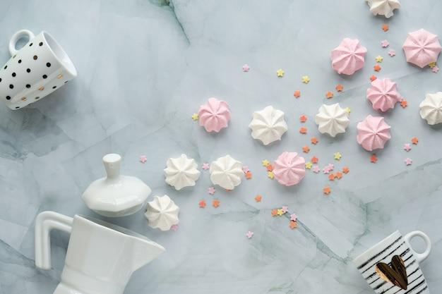 Lay plano criativo com xícara de café, máquina de café expresso em cerâmica e marshmallows na mesa de mármore.