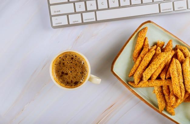 Layflat vista para um com café e batatas fritas teclado de computador