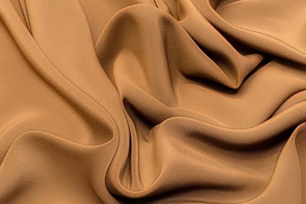 Layout artístico em tecido de seda crepe de chine marrom. textura, plano de fundo. modelo.
