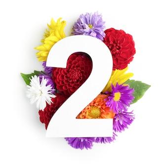 Layout com flores coloridas, folhas e número dois. postura plana. vista do topo.